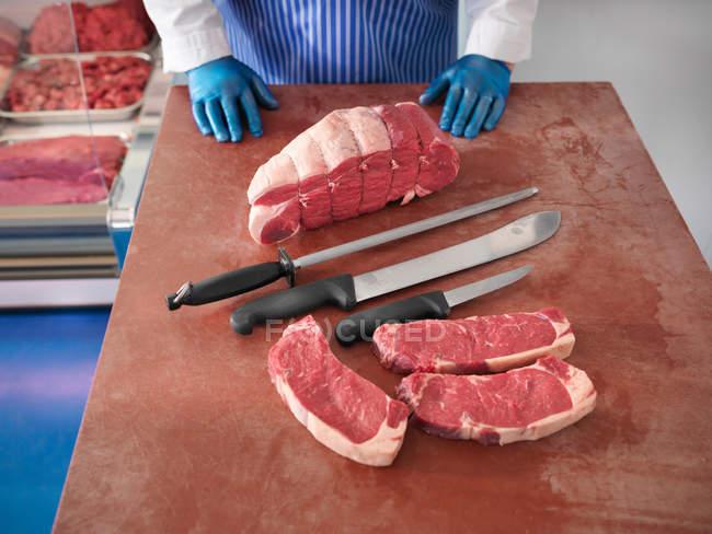 Carnicero con cuchillos y cortes de cerdo - foto de stock