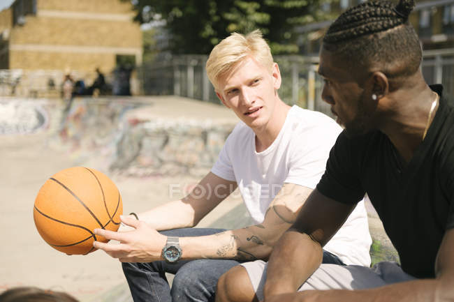 Two young male basketball players chatting in city skatepark — Stock Photo