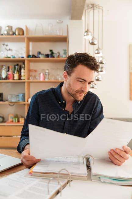 Mulher olhando para a papelada enquanto se senta à mesa em casa — Fotografia de Stock