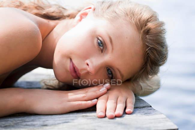 Donna sdraiata su un bacino di legno — Foto stock