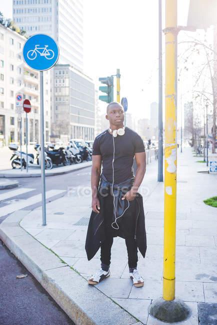 Юнак стоячи автомобільним транспортом, навушників шиї, хтось дивитися вбік — стокове фото