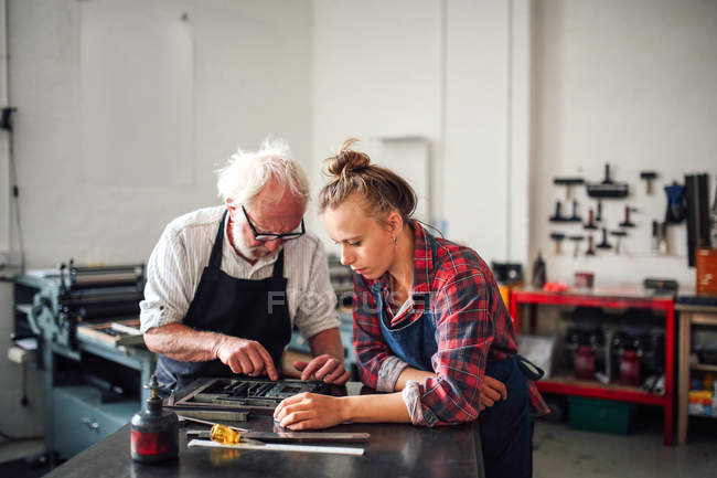 Senior craftsman working on letterpress with young craftswoman in print workshop — Stock Photo