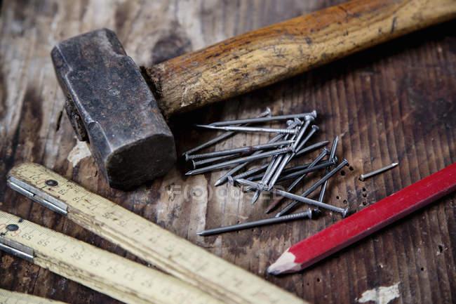 Крупним планом олівець, нігті, молоток, zig zag лінійки на дерев'яні поверхні — стокове фото