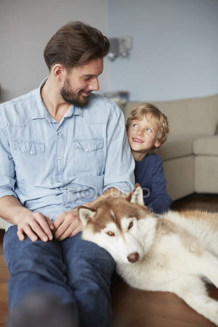 Father and son sitting with dog face to face smiling — Stock Photo