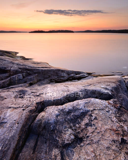 Long expposure shot of rocky lakeside in sunset light — Stock Photo