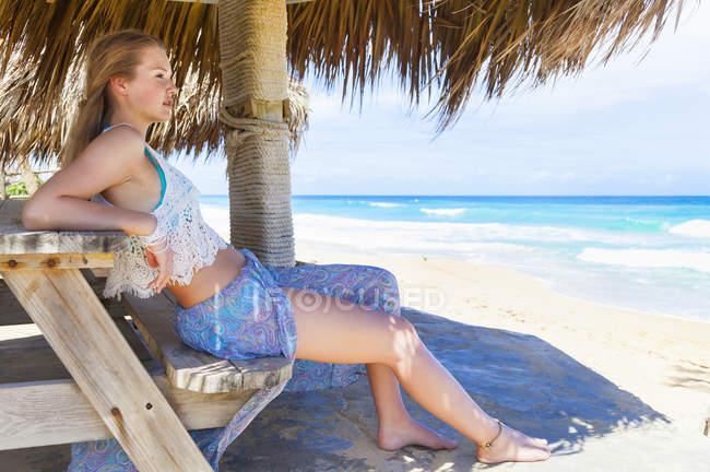 Молодая женщина, глядя из пляж пикник скамьи, Доминиканская Республика, в Карибском бассейне — стоковое фото