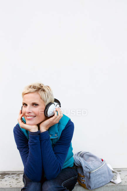 Smiling woman listening to headphones — Stock Photo