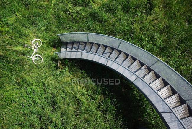 Bicicleta en hierba bajo escalera de caracol - foto de stock