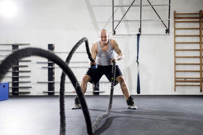 Man training with battling ropes in gym — Stock Photo