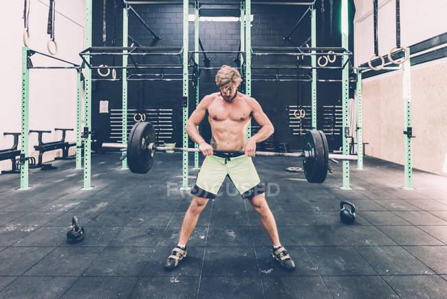 Jeune homme haltères haltérophilie en croix formation gym — Photo de stock