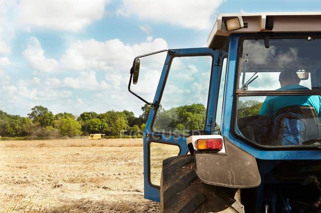 Paysan assis en tracteur dans le champ de la culture — Photo de stock