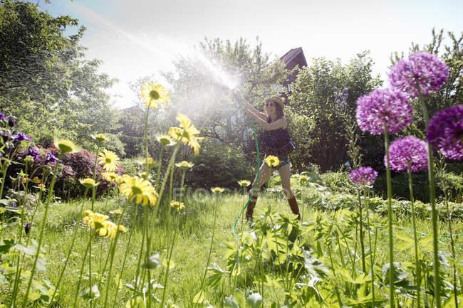 Ver os através das flores de mulher madura no jardim flores regas com mangueira — Fotografia de Stock