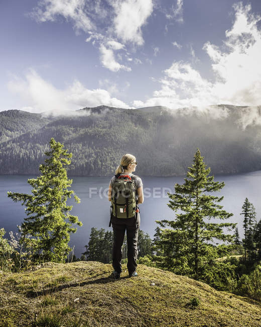 Female hiker looking out over Comox Lake, Coutenay, Vancouver Island, British Columbia, Canada — Stock Photo