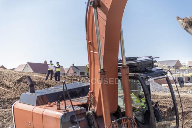 Экскаватор и строители на строительной площадке — стоковое фото