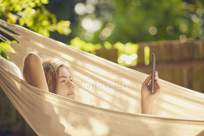 Мальчик-подросток лежит в саду гамак просматривая цифровые таблетки — стоковое фото