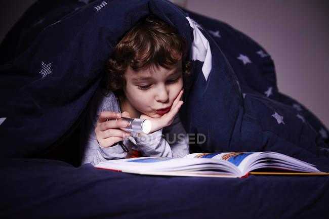 Menino sob edredão leitura livro por tocha — Fotografia de Stock
