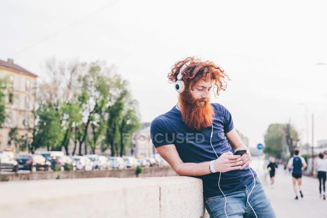 Молодой хипстер с рыжими волосами и бородой выбирает музыку для наушников в городе — стоковое фото