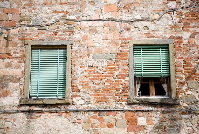 Terracotta brick wall of building facade with windows — Stock Photo
