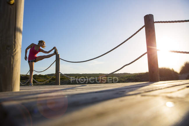Woman stretching on boardwalk at daytime — Stock Photo