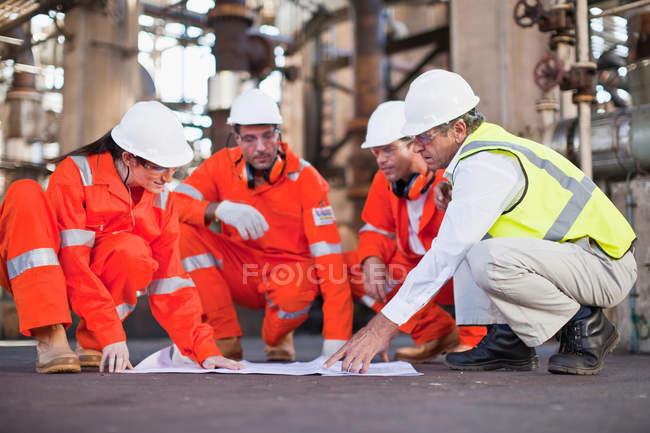 Trabalhadores com projetos na refinaria de petróleo, foco seletivo — Fotografia de Stock