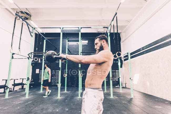 Young male cross trainer weightlifting kettlebell in gym — Stock Photo