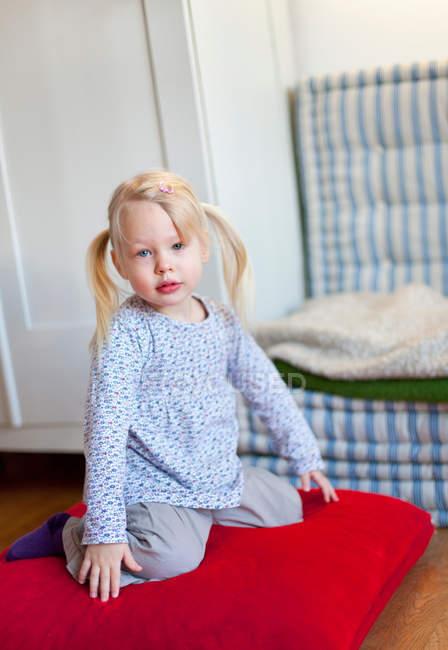 Chica sentada en la almohada en la sala de estar - foto de stock