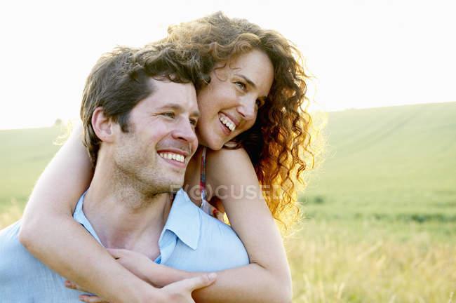 Mann trägt Frau in einem Weizenfeld — Stockfoto