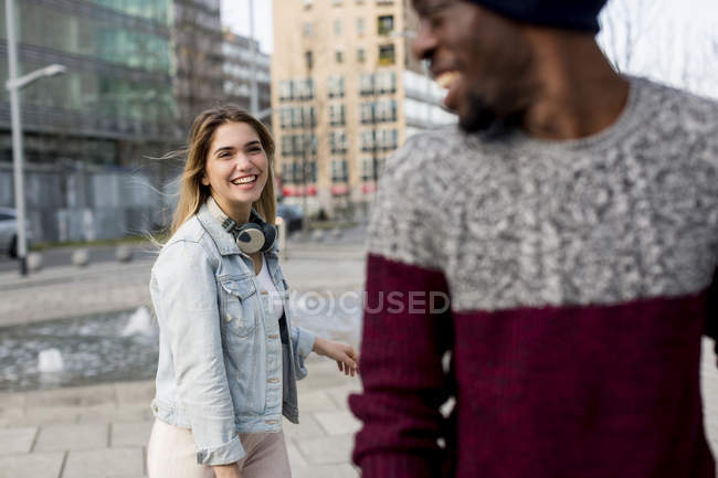 Multi ethnic couple laughing in street — Stock Photo