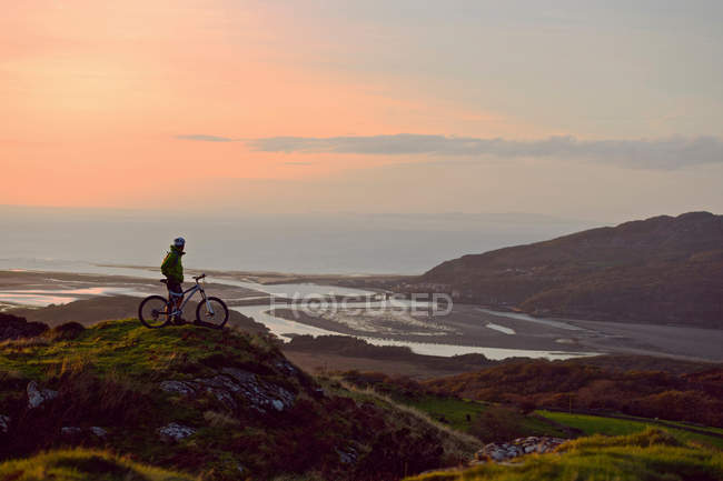 Велосипедист стоит на вершине холма — стоковое фото