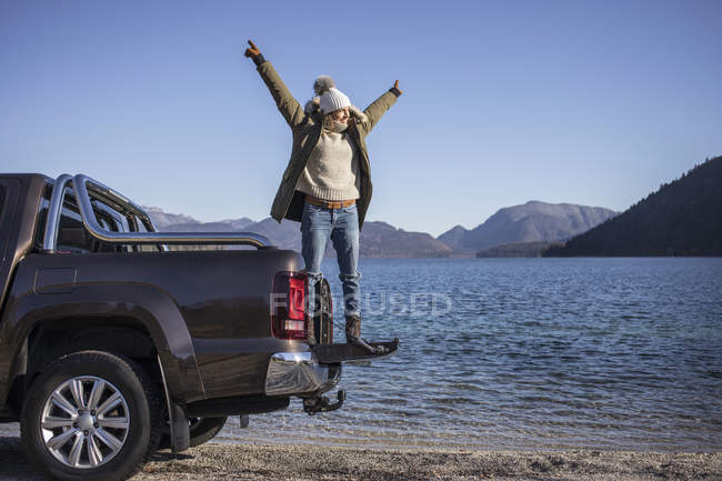 Woman with arms open standing on pick up at lakeside in Bavarian Alps — Stock Photo
