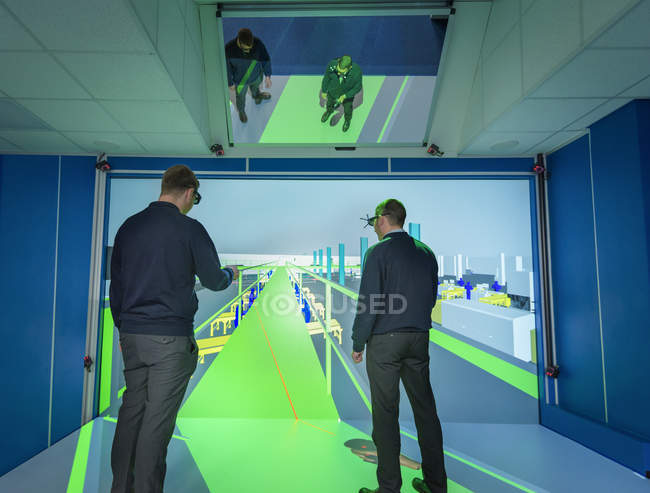 Engineers inspecting factory layout in 3D in virtual reality suite — Stock Photo