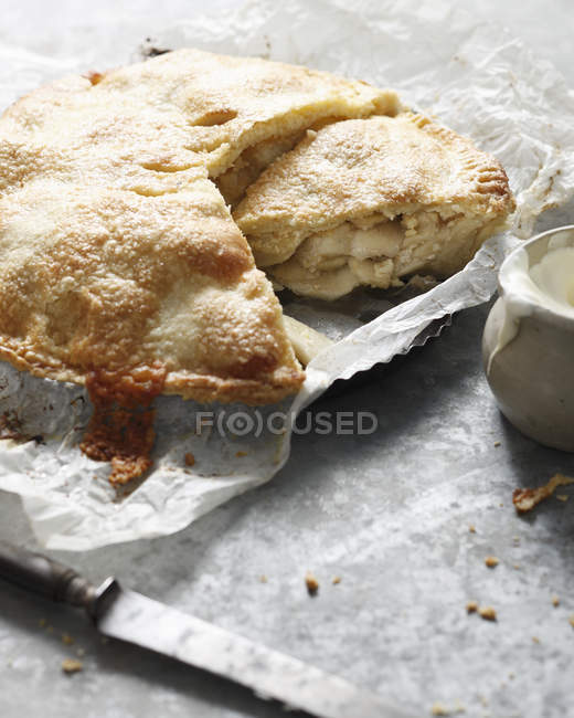Homemade apple cheddar pie with knife and jug of cream on table — Stock Photo