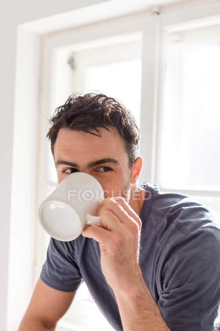 Чоловік п'є з кухля на дому — стокове фото