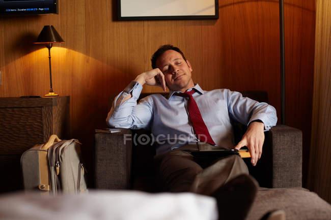 Empresario durmiendo en habitación de hotel - foto de stock