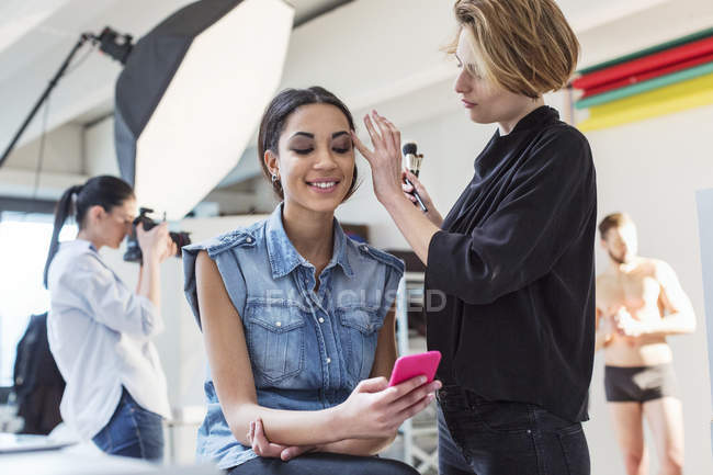 Make up artist applying eye shadow to model in photography studio — Stock Photo