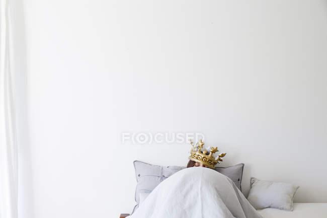 Mature woman in bed underneath quilt wearing golden crown — Stock Photo