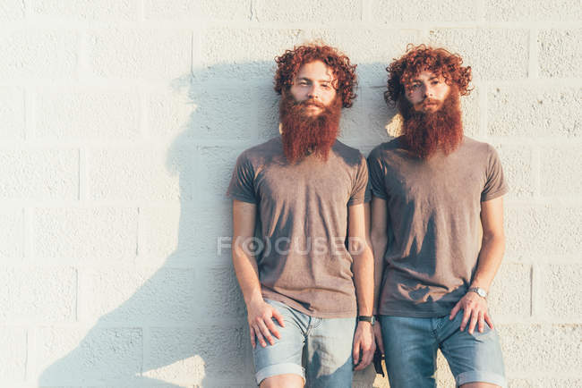 Portrait of identical adult male twins with red hair and beards against wall — Stock Photo