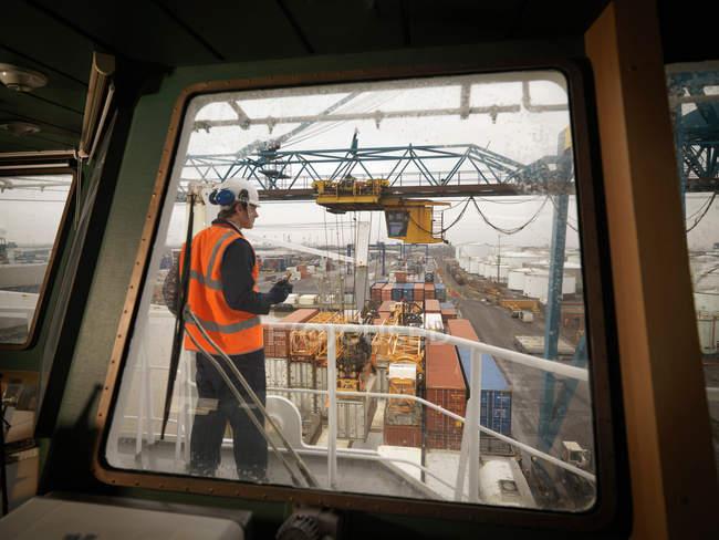 Портовый рабочий контролирует загрузку судна — стоковое фото