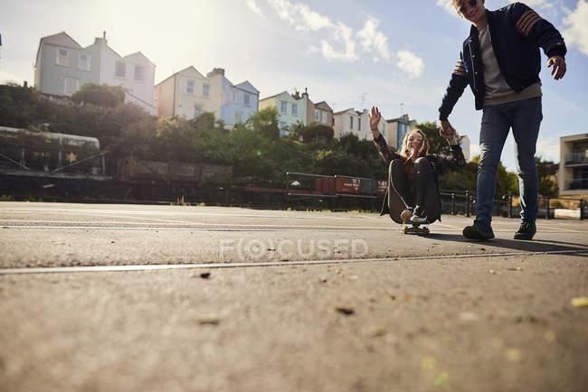 Due amici a scherzare, giovane uomo che tira la giovane donna lungo su skateboard, Bristol, Regno Unito — Foto stock