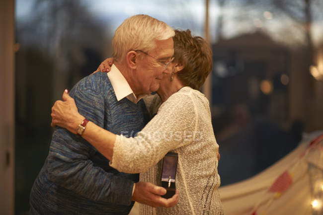 Romantic senior couple hugging while holding gift box — Stock Photo