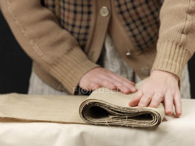 Coupées en gros plan de jeunes femelle concepteur mains pliage tissu de toile de jute — Photo de stock