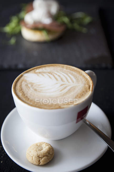 Cup of cappuccino with biscuit and spoon on table — Stock Photo