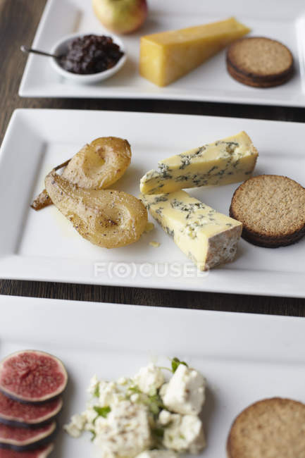 Plates with different cheese and fruits on table — Stock Photo