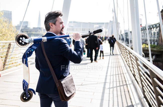Businessman carrying scooter, Hungerford Bridge, London, UK — Stock Photo