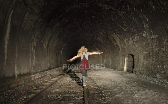 Girl in deserted railway tunnel, walking along track, rear view — Stock Photo