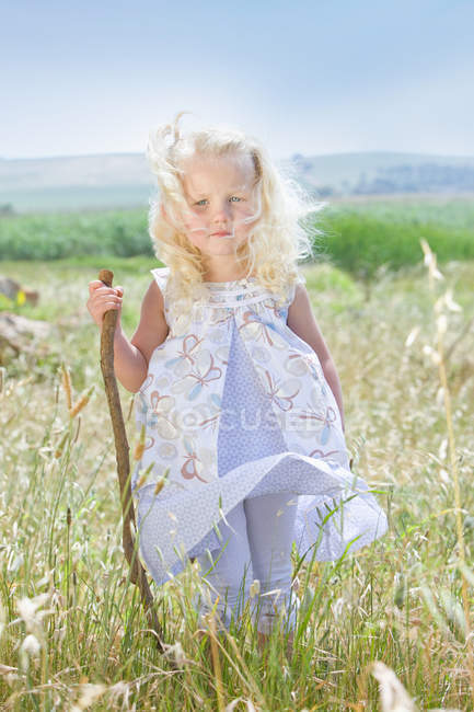 Toddler girl standing in tall grass — Stock Photo