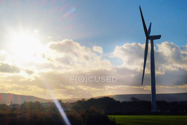 Sun lighted sky and wind turbine in rural landscape — Stock Photo