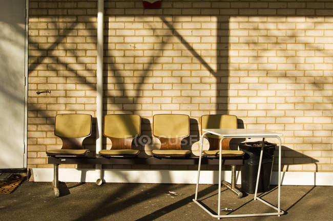 Row of chairs outside building in sunlight — Stock Photo