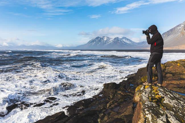 Hombre parado en la roca, fotografiando la vista, Hvalnes. Islandia - foto de stock