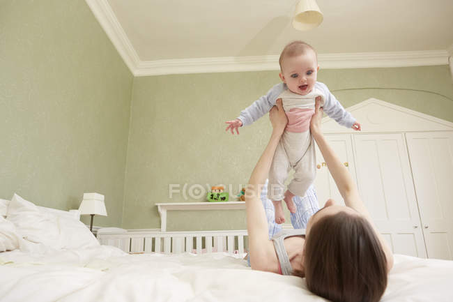 Women lying on bed holding up baby daughter — Stock Photo